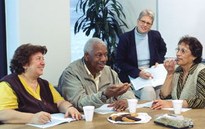 Four people sitting at conference room table, talking.