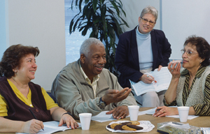Adults sitting around table talking with group facilitator present.