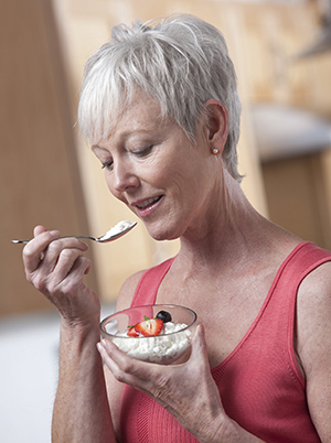 Woman eating a bowl of cottage cheese and fruit.