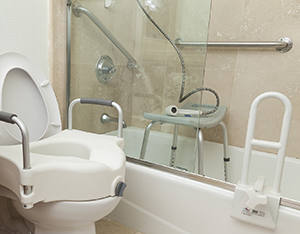 Bathroom set up with grab bars, commode seat, and other safety features.